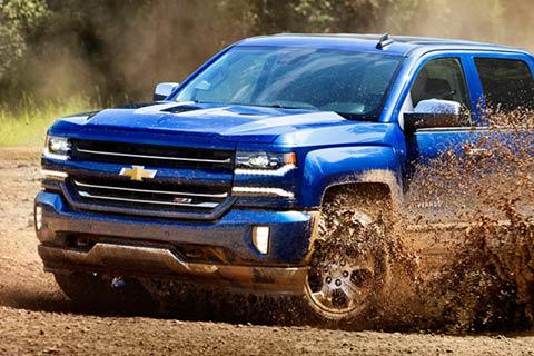 A blue truck driving through mud