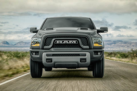 A black truck with a prominent RAM grille driving towards the viewer